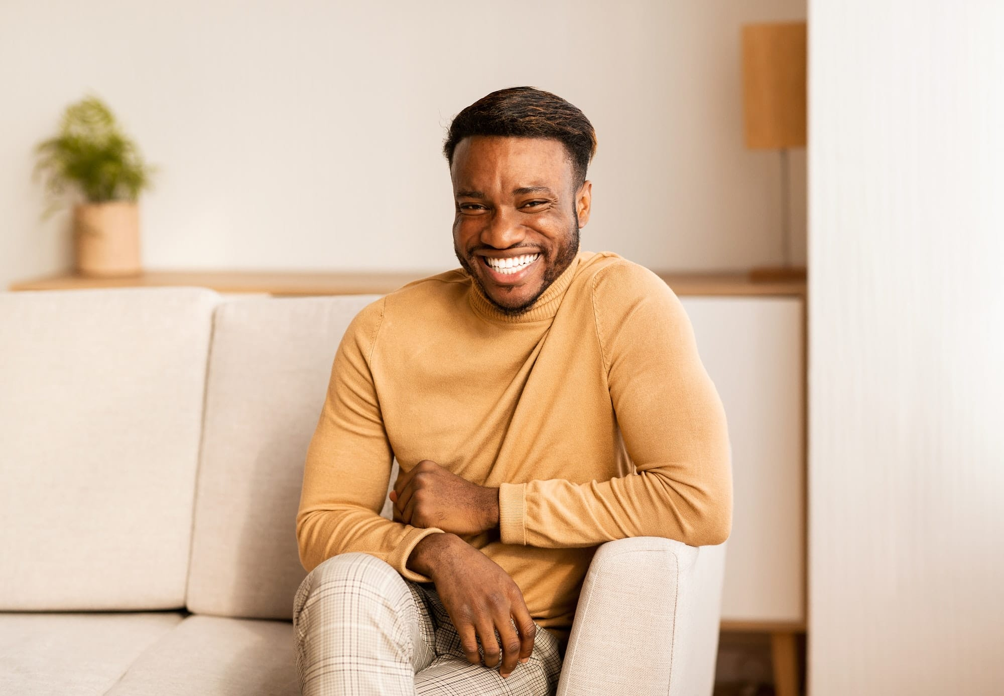 Afro Guy Smiling At Camera Sitting On Sofa At Home