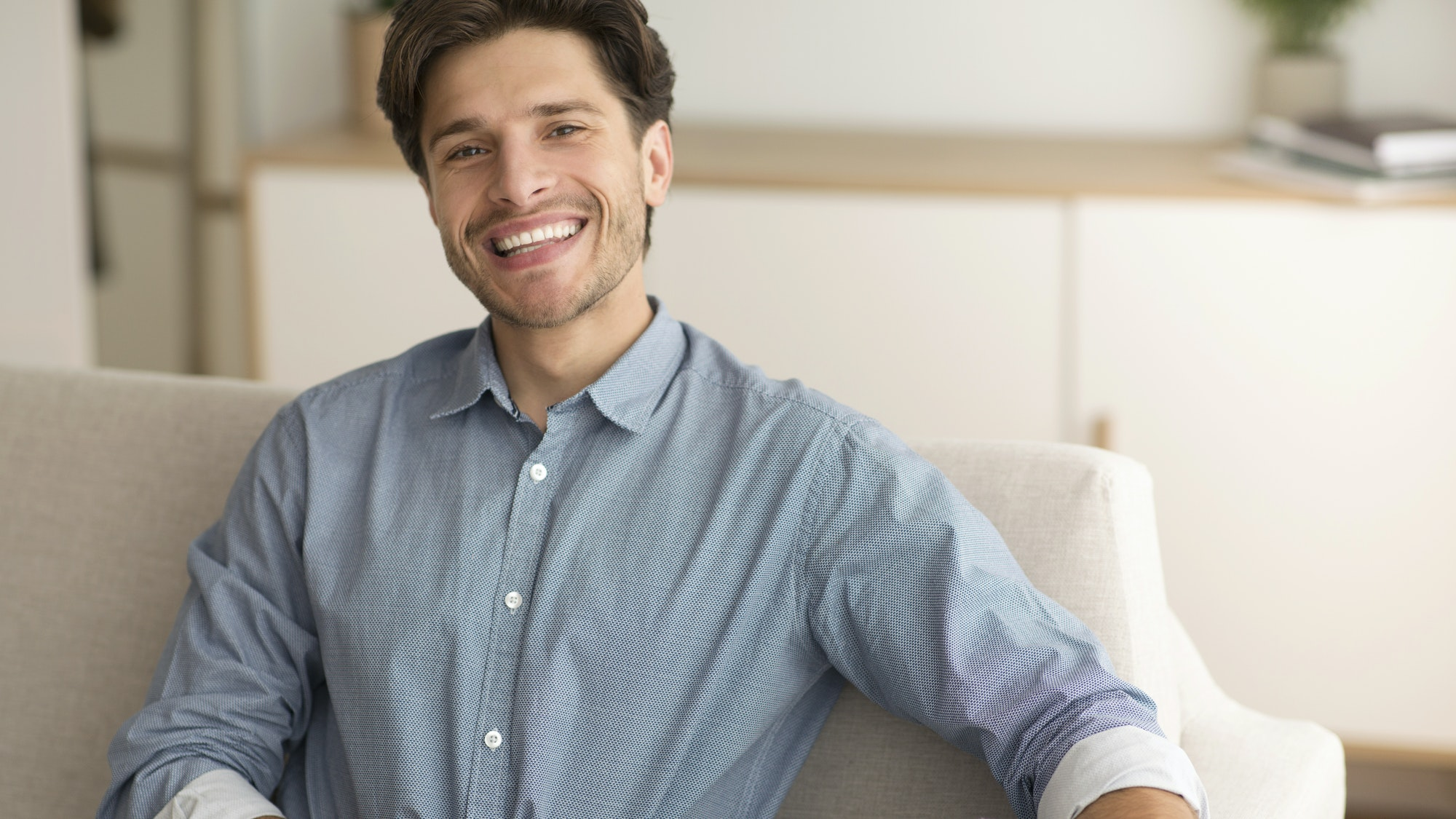 Cheerful Guy Smiling At Camera Resting On Couch At Home