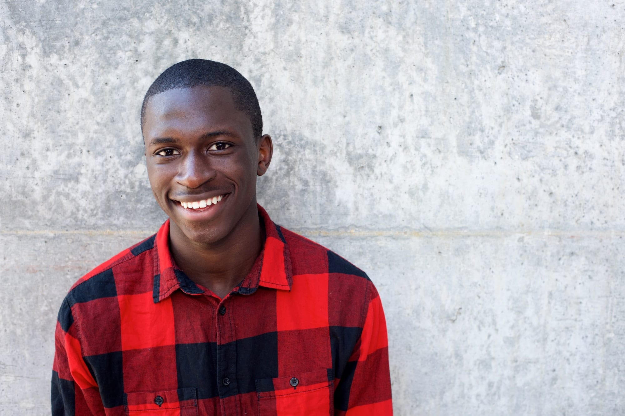 Smiling young african male model standing against wall