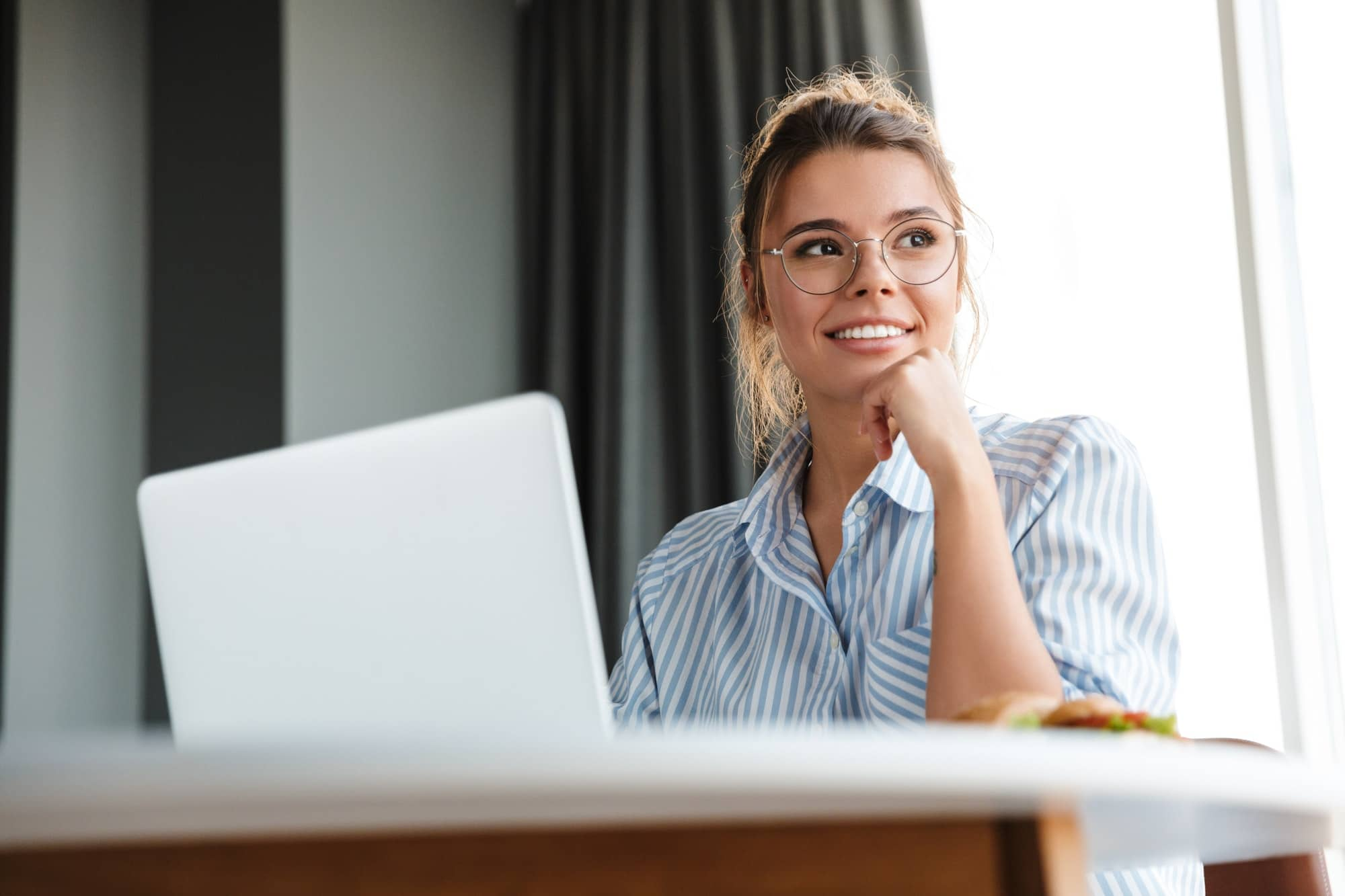 Image of happy nice woman working with laptop and smiling