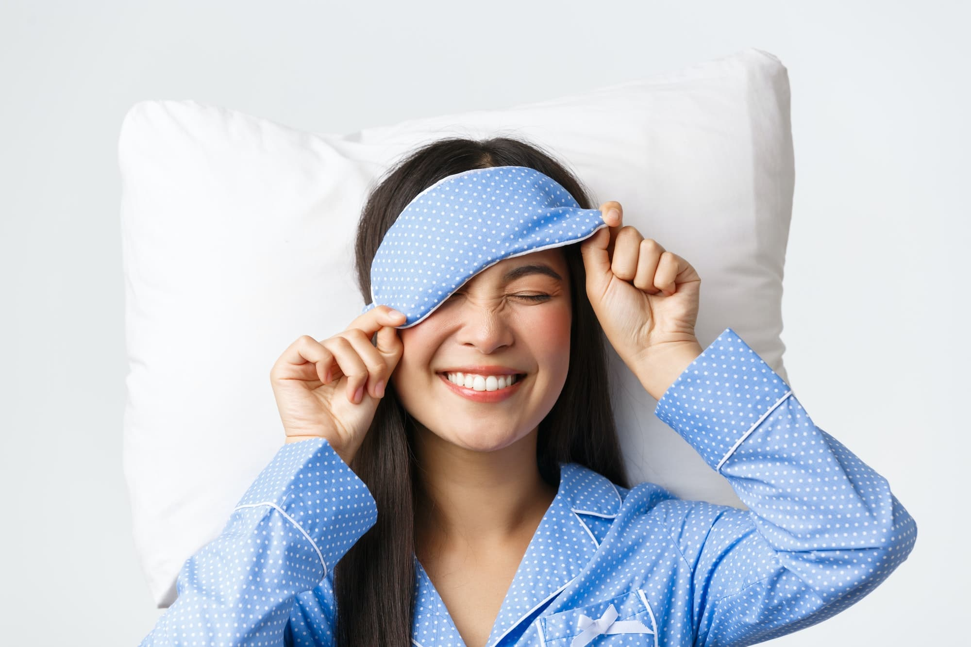 Pleased happy smiling korean girl in blue pajamas and sleeping mask, had great day going bed in